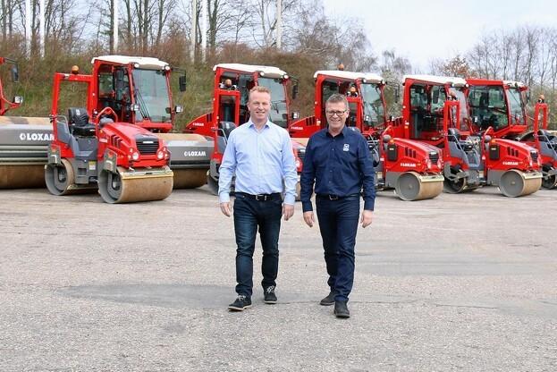 De to hovedaktører i handelen med tæt på 75 tons tromlende maskineri skridter fronten af, før de 14 maskiner sendes fra Wirtgen Denmark i Taulov til Loxam-afdelinger landet over. Loxams tekniske chef Frank Larsen (til venstre) og salgskonsulent Finn Nielsen fra Wirtgen Denmark. Pressefoto.